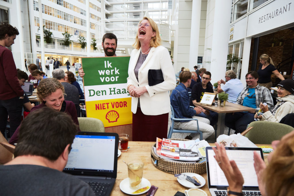 """Den Haag - Den Haag, 1 september 2018 - Haagse burgemeester Pauline Krikke (VVD) groet een groep milieuactivisten in het stadhuis van Den Haag. Vanochtend tussen 8 en 9.30 uur protesteerden zo'n 50 mensen voor de hoofdingang van het Haagse stadhuis tegen de invloed van Shell op de lokale energietransitie. Ze eisen van gemeente Den Haag dat de benoeming van Marjan van Loon tot adviseur energietransitie van de gemeente bij The Hague Economic Board wordt teruggedraaid.  Vanuit de Economic Board zou Shell-CEO Marjan van Loon GroenLinks-wethouder Liesbeth van Tongeren adviseren over de lokale energietransitie. Stein Smit bood de wethouder namens Dwars Leiden-Haaglanden een ingelijste poster aan met de tekst 'Ik werk voor Den Haag, niet voor Shell'. Smit: """"Die is voor op uw werkkamer. Als u ongewenst bezoek krijgt van iemand als Marjan van Loon, hoeft u er alleen maar naar te wijzen.""""  """"De benoeming van Marjan van Loon maakt duidelijk dat het stadsbestuur alleen naar Shell kijkt als belangrijke werkgever,"""" sprak Femke Sleegers van Den Haag Fossielvrij. """"Voor de zwarte kanten van de multinational sluit het college de ogen.""""   Den Haag Fossielvrij, Dwars, ROOD en Pink kondigden aan dat ze blijven protesteren tot de gemeente de benoeming terugdraait. Tot die dag voert Den Haag wat hen betreft een nieuw logo; het logo van Shell met daaronder de woorden 'conflict en onrecht'.  Om de invloed van Shell op het stadhuis te symboliseren, legden de actievoerders vanochtend een grote opgeblazen 'oliebuis' in Shell-kleuren voor de hoofdingang van het stadhuis. Ambtenaren moesten er overheen klimmen en gingen op de foto met een bord 'Ik werk voor Den Haag, niet voor Shell."""" - COPYRIGHT PIERRE CROM / Den Haag Fossielvrij Photo: Pierre Crom"""