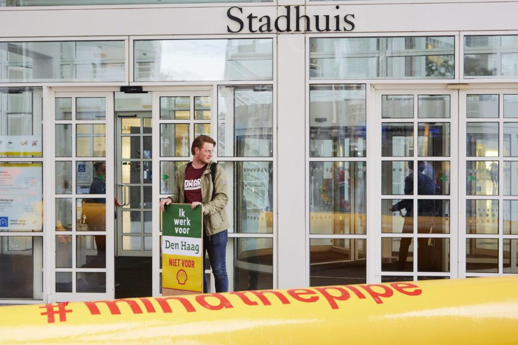 """Den Haag - Den Haag, 1 september 2018 - Vanochtend tussen 8 en 9.30 uur protesteerden zo'n 50 mensen voor de hoofdingang van het Haagse stadhuis tegen de invloed van Shell op de lokale energietransitie. Ze eisen van gemeente Den Haag dat de benoeming van Marjan van Loon tot adviseur energietransitie van de gemeente bij The Hague Economic Board wordt teruggedraaid.  Vanuit de Economic Board zou Shell-CEO Marjan van Loon GroenLinks-wethouder Liesbeth van Tongeren adviseren over de lokale energietransitie. Stein Smit bood de wethouder namens Dwars Leiden-Haaglanden een ingelijste poster aan met de tekst 'Ik werk voor Den Haag, niet voor Shell'. Smit: """"Die is voor op uw werkkamer. Als u ongewenst bezoek krijgt van iemand als Marjan van Loon, hoeft u er alleen maar naar te wijzen.""""  """"De benoeming van Marjan van Loon maakt duidelijk dat het stadsbestuur alleen naar Shell kijkt als belangrijke werkgever,"""" sprak Femke Sleegers van Den Haag Fossielvrij. """"Voor de zwarte kanten van de multinational sluit het college de ogen.""""   Den Haag Fossielvrij, Dwars, ROOD en Pink kondigden aan dat ze blijven protesteren tot de gemeente de benoeming terugdraait. Tot die dag voert Den Haag wat hen betreft een nieuw logo; het logo van Shell met daaronder de woorden 'conflict en onrecht'.  Om de invloed van Shell op het stadhuis te symboliseren, legden de actievoerders vanochtend een grote opgeblazen 'oliebuis' in Shell-kleuren voor de hoofdingang van het stadhuis. Ambtenaren moesten er overheen klimmen en gingen op de foto met een bord 'Ik werk voor Den Haag, niet voor Shell."""" - COPYRIGHT PIERRE CROM / Den Haag Fossielvrij Photo: Pierre Crom"""